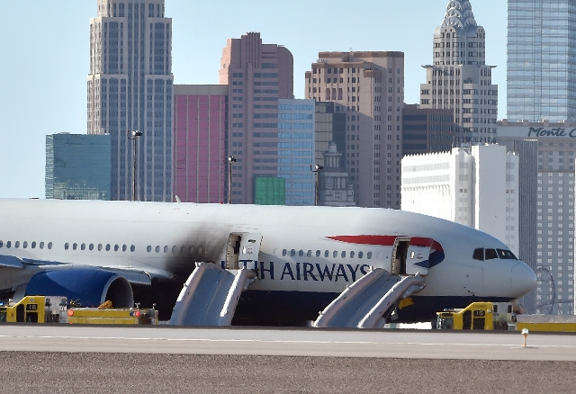 A British Airways passenger jet is parked on the runway after an onboard fire broken out at McCarran International Airport on Tuesday, Sept. 8, 2015. The Boeing 777-200 was headed to Gatwick Airpo ...