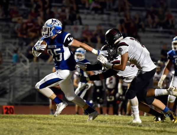 Basic's Jake Waldren breaks free from Desert Oasis' defenders as he rushes for his second touchdown during the first half of a high school football game at Basic High School Friday, Se ...
