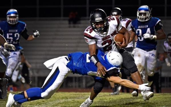 Basic's Kyle Grismanauskas (2) dives for the tackle against Desert Oasis' Ty'shun McClinton during the first half of a high school football game at Basic High School Friday, Sept ...