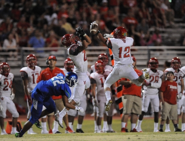 Arbor View safety Staycee Robinson (25) and defensive back Noah Noce (12) break up a pass intended for Green Valley wide receiver Brayon Williams (22) in the second quarter of their high school fo ...