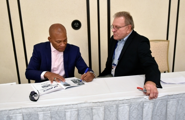 Lee Kemp, left and Russ Hellickson sign autographs before an International Fraternity of Wrestlers dinner honoring the 1980 Olympic wrestling team at the Gold Coast hotel-casino on Friday, Sept. 1 ...