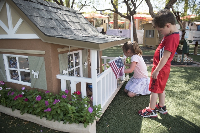"Three-year-old Rocco Cicchetti and his five-year-old sister Bella Cicchetti check out ""The Mutt Hutt"" dog house, one of several raffle prizes at the Southern Nevada Home Builders Associa ..."