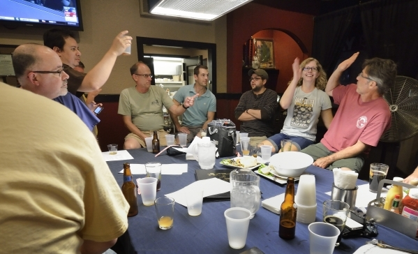 Cory Roth, right, gets a high-five from Diana Hull after he correctly guessed the type of mystery beer he sampled during a tasting at a meeting of the Southern Nevada Ale Fermenting Union at Aces  ...