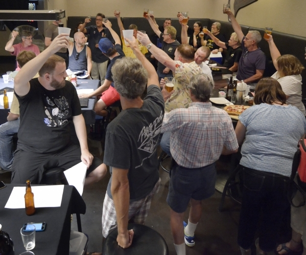 Members of the Southern Nevada Ale Fermenting Union raise their glasses in toast toward the end of a meeting at Aces and Ales at 3740 S. Nellis Blvd. in Las Vegas on Friday, Sept. 11, 2015. Bill H ...