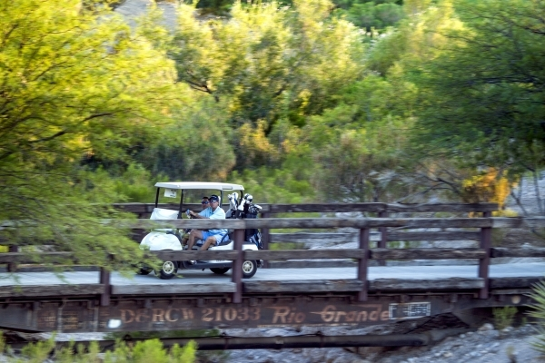 Golfer rides a cart at Badlands Golf Course, 9119 Alta Drive, on Thursday, Sept. 10,2015.EHB Companies, the developers behind high-end retail center Tivoli Village, confirmed it had bought the cas ...