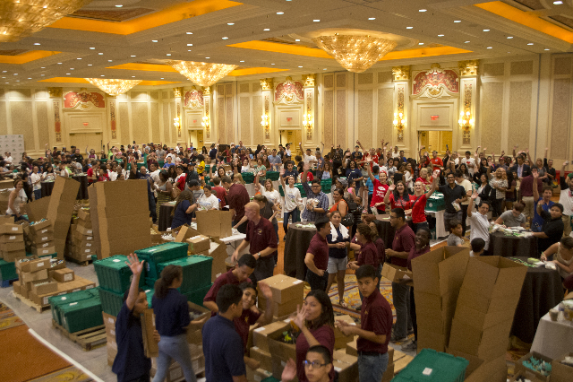 Hundreds of volunteers wave during an event run by Clean the World inside the Sands Expo and Convention Center on the Strip poised to build 200,000 hygiene kits for the homeless on Saturday, Sept. ...