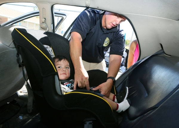 Clark County School District Police Officer Tony Thalman secures Fabian Alarcon, 10 months, into a new car seat while giving instructions to his mother during a National Seat Check Saturday near K ...