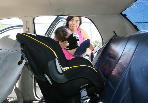 Ofelia Alarcon lifts her son Fabian, 10 months, to place him in a new car seat the family received while attending National Seat Check Saturday near Katz Elementary School Saturday, Sept. 19, 2015 ...