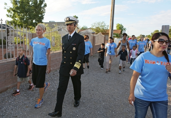 U.S. Surgeon General Vivek Murthy, center, walks with Myrtle Tate Elementary School Principal Sarah Popek, second from left, and her son Trystan Popek, 6, left, during a group walk at the school T ...