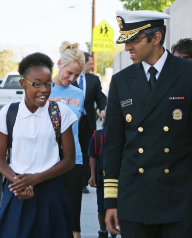 U.S. Surgeon General Vivek Murthy, right, walks with student Jumanah Perkins, 10, during a group walk outside Myrtle Tate Elementary School Tuesday, Sept. 15, 2015, in Las Vegas. Murthy visited th ...