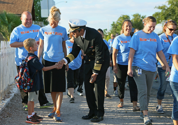 U.S. Surgeon General Vivek Murthy, center, pauses to shake hands with student Trystan Popek, 6, left, during a group walk outside Myrtle Tate Elementary School Tuesday, Sept. 15, 2015, in Las Vega ...