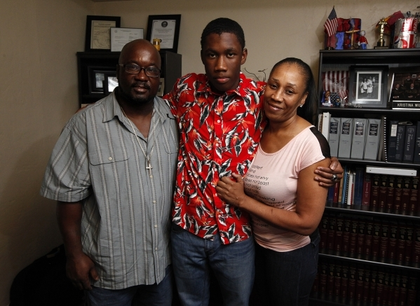Patrick Harper, center, stands in his lawyer's office flanked by his parents Wayne Harper Sr., left, and Latreavor Henderson, right, in downtown Las Vegas on Wednesday, Sept. 24, 2014. Harpe ...