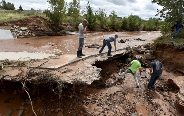 Residents search along the Short Creek bank after a flash flood in Hildale, Utah September 15, 2015. At least eight people were killed near Utah's border with Arizona when flash floods trigg ...
