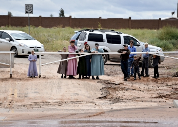 Residents watch rescuers search along the Short Creek after a flash flood in Hildale, Utah September 15, 2015. At least eight people were killed near Utah's border with Arizona when flash fl ...