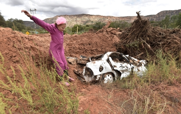 A girl jumps off a mound of dirt that was piled up with one of the vehicles found after a flash flood, in Hildale, Utah September 15, 2015. Flash floods killed nine people near Utah's border ...
