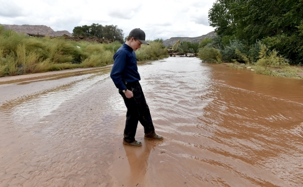 "A young resident crosses the Short Creek after a flash flood in Hildale, Utah September 15, 2015. Flash floods killed nine people near Utah's border with Arizona when a ""large wall of w ..."