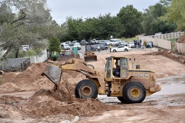 """A construction equipment clears debris after a flash flood in Hildale, Utah September 15, 2015. Flash floods killed nine people near Utah's border with Arizona when a """"large wall of wat ..."""