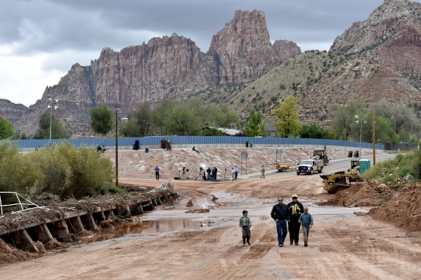 """Residents walk across one of the many flooded streets after a flash flood in Hildale, Utah September 15, 2015. Flash floods killed nine people near Utah's border with Arizona when a """"la ..."""