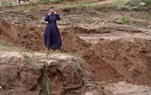 A resident takes pictures of an estimated 50-foot deep gorge that was created after a flash flood in Hildale, Utah September 15, 2015. At least eight people were killed near Utah's border wi ...