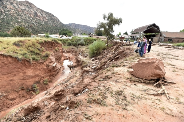 Residents look down an estimated 50-foot deep gorge that was created after a flash flood in Hildale, Utah September 15, 2015. At least eight people were killed near Utah's border with Arizon ...