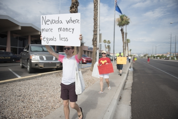 Clark County School District teachers Andy Lotte, left, and Shannon Hale picket with fellow teachers outside of the district's Edward Greer Education Center in Las Vegas on Thursday, July 2, ...