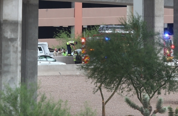 Nevada Highway Patrol and Las Vegas Fire and Rescue respond the scene where a man jumped to his death from the the U.S. Highway 95 northbound flyover ramp to Interstate 15 in Las Vegas on Tuesday, ...