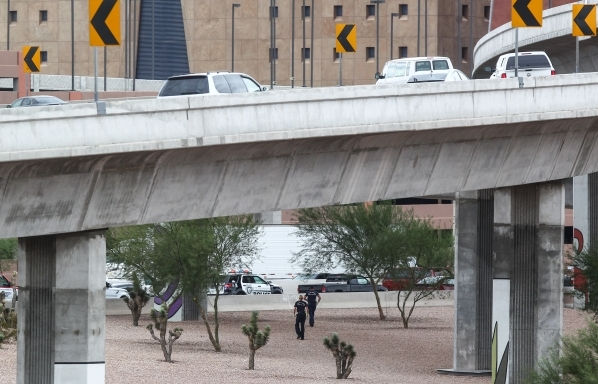 Las Vegas Fire and Rescue paramedics attempt to reach the scene where a man jumped to his death from the the U.S. Highway 95 northbound flyover ramp to Interstate 15 in Las Vegas on Tuesday, Sept. ...