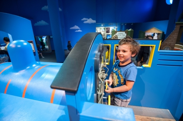 Comfy in Thomas the Tank Engine's cab, a young engineer can flip levers and investigate other working parts that trigger whistles and steam as part of a new touring exhibit that pulls into t ...