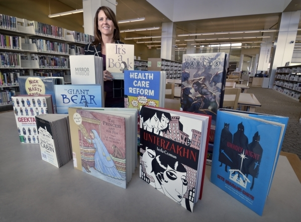 Kathy DiGeorge, young peoples collection librarian at the Windmill Library, is shown at the library on Friday, Sept. 18, 2015, with books which some patrons felt contained objectionable content. B ...