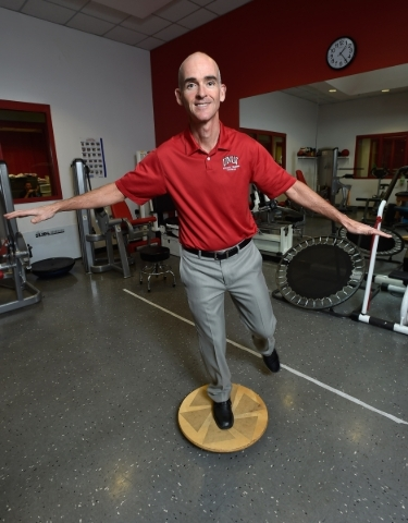Tedd Girouard, UNLV's director of athletic training, uses a balancing device as he poses at UNLV on Monday, Sept. 21, 2015. Balance is a key determination when testing for determining a poss ...