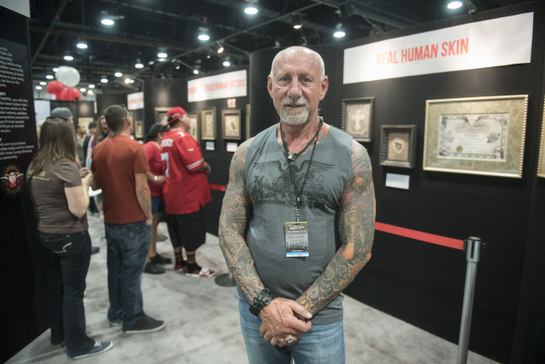 """Charles Hamm, owner of Save My Ink poses at the Nation Association for the Preservation of Skin Art booth at the """"Biggest Tattoo Show on Earth"""" at the Las Vegas Convention Center Las Veg ..."""
