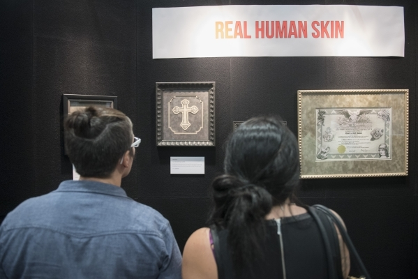 """Attendees view framed and preserved tattoos on real human skin at the Nation Association for the Preservation of Skin Art booth at the """"Biggest Tattoo Show on Earth"""" at the Las Vegas Con ..."""