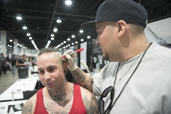 "David ""Vandal"" Ruiz, right, of the shop Skin Design Tattoo Las Vegas, prepares to tattoo Las Vegas local Pat Urquidi at the ""Biggest Tattoo Show on Earth"" at the Las Vegas Conv ..."
