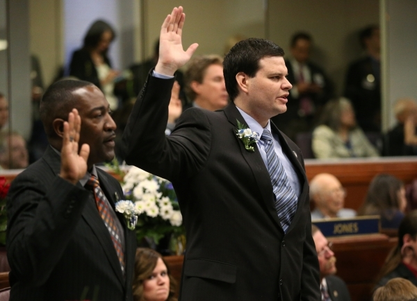 Nevada Assemblymen Tyrone Thompson, D-North Las Vegas, left, and David Gardner, R-Las Vegas, take the oath of office during opening day ceremonies at the Legislative Building in Carson City, Nev., ...