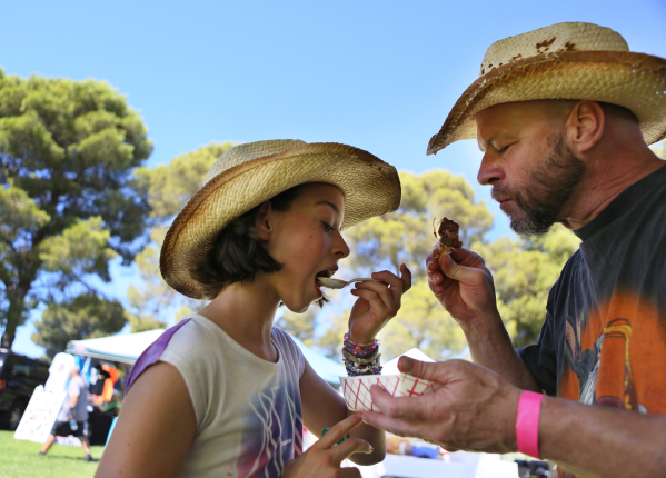 Marina Saeger, 10, left, shares a meal with her father Bob during the Pigs for Kids Barbecue Cook-Off and Festival at Craig Ranch Regional Park Saturday, Sept. 19, 2015, in North Las Vegas. Ronda  ...