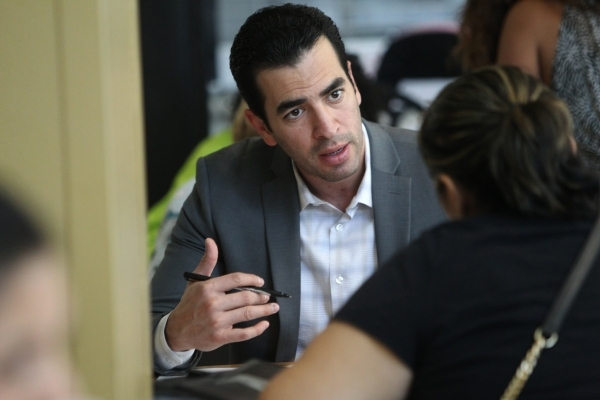Sen. Ruben Kihuen, D-Las, helps fill out paperwork during a citizenship workshop hosted by local progressive groups, labor groups and immigration attorneys inside the June Whitley Student Center a ...