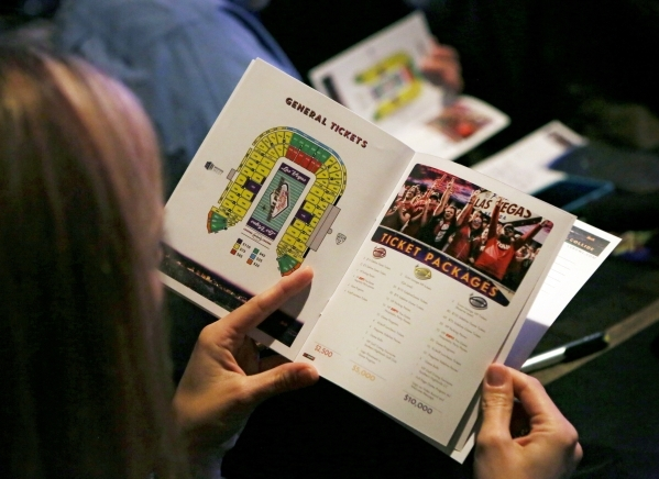 People look through ticket packages during a Royal Purple Las Vegas Bowl ticket kickoff luncheon at the Hard Rock hotel-casino Wednesday, Sept. 23, 2015, in Las Vegas. Former Oregon football coach ...