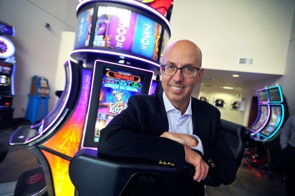 Scientific Games CEO Gavin Isaacs poses with a Cirque du Soleil-themed slot machine at the company headquarters on Friday, Sept. 25, 2015, in Las Vegas. (David Becker/Las Vegas Review-Journal)