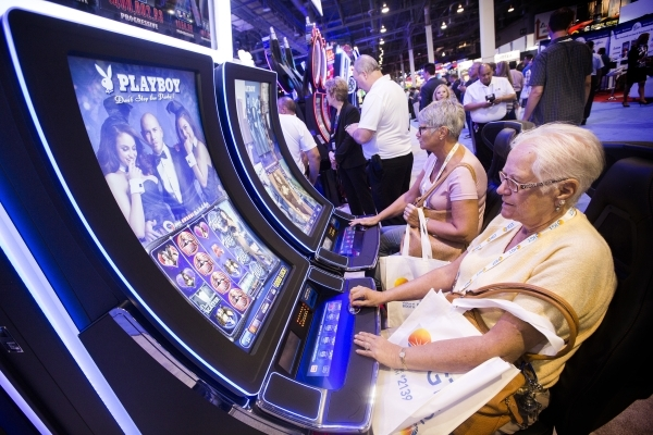 Sharon Baranowski, left, and Theresa Lonski play the Playboy slot featuring Pitbull in the Scientific Games booth at the Global Gaming Expo in the Sands Expo and Convention Center on Wednesday, Se ...