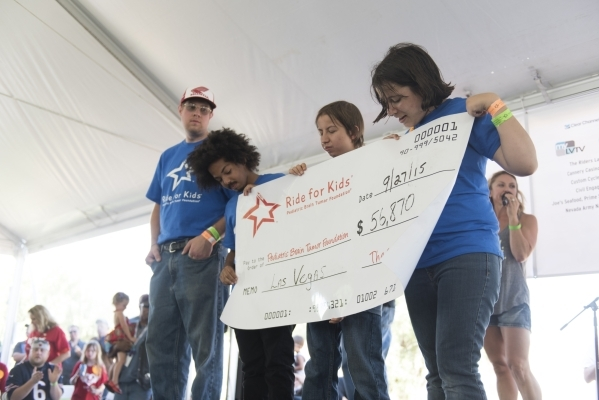 Brain cancer survivors, from left, Towbin Volberding, Brandon Savoy, Bradley Stanton, 17, and Hannah Wilker, 13 hold a novelty check showing how much money was raised during the Ride for Kids bene ...