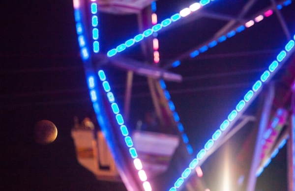 """The """"blood moon"""" rises as people go on a ferris wheel during the Life is Beautiful festival in downtown Las Vegas on Sunday, Sept. 27, 2015. Chase Stevens/Las Vegas Review-Journal Follow ..."""