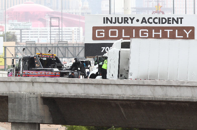 A tow truck driver prepares to tow a tractor-trailer that hit a wall on the ramp from southbound U.S. Highway 95 to southbound Interstate 15 in Las Vegas on Tuesday, Sept. 15, 2015. Chase Stevens/ ...
