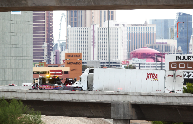 A tow truck driver hauls a tractor-trailer that hit a wall on the ramp from southbound U.S. Highway 95 to southbound Interstate 15 in Las Vegas on Tuesday, Sept. 15, 2015. Chase Stevens/Las Vegas  ...