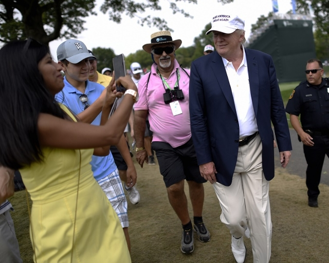 Aug 30, 2015; Edison, NJ, USA;  Presidential candidate and businessman Donald Trump greets golf fans near the 2nd tee during the final round of The Barclays at Plainfield Country Club. (Eric Sucar ...