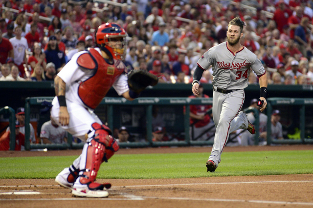 Aug 31, 2015; St. Louis, MO, USA; Washington Nationals right fielder Bryce Harper (34) scores on a double by first baseman Ryan Zimmerman (not pictured) as St. Louis Cardinals catcher Yadier Molin ...