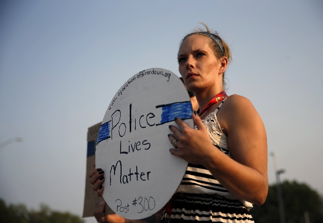 A supporter of Fox Lake Police Lt. Charles Joseph Gliniewicz stands on the side of the road in memory of the slain police officer in Fox Lake, Illinois, Sept. 1, 2015.  (Jim Young/Reuters)