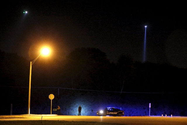 Police helicopters use searchlights on the wooded areas for the killers of slain Fox Lake Police Lt. Charles Joseph Gliniewicz in Fox Lake, Illinois, Sept. 1, 2015. (Jim Young/Reuters)