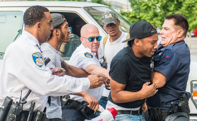 A man fights with police as protests moved into the street on the first day of pretrial motions for six police officers charged in connection with the death of Freddie Gray in Baltimore, Sept. 2,  ...