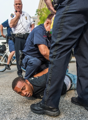 A protester is restrained after fighting with police as protests moved into the street on the first day of pretrial motions for six police officers charged in connection with the death of Freddie  ...
