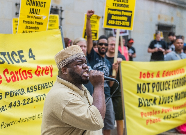 Activist C.D. Witherspoon speaks to a small crowd gathered outside of the courthouse on the first day of pretrial motions for six police officers charged in connection with the death of Freddie Gr ...